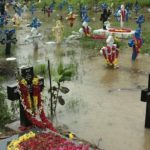 Rain falls steadily as people remember the dead at cemeteries