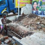 Civic workers de-silt drains on San Thome High Road