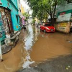 Politician and civic activist taps flooded water on street - for good use