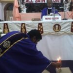 People light candles inside church to remember the dead on All Souls Day
