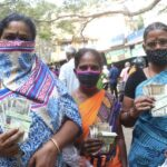 People queue at ration shops to pick up Pongal special package
